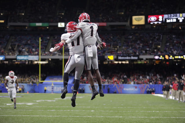 Georgia wide receiver George Pickens celebrates with teammate Eli Wolf. Pickens had 12 catches against Baylor. (AP Photo/Brett Duke)