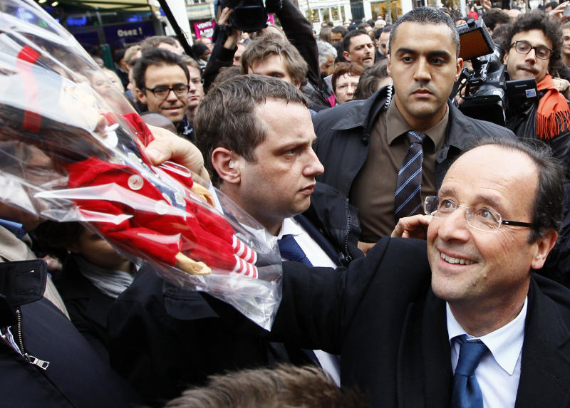 "French Socialist Party candidate for the 2012 presidential elections Francois Hollande, right, receives a traditional local puppet representing a ""Comedy Valet with Big Heart"" called ""La Fleur"" as a gift during a campaign meeting in Amiens, northern France, Wednesday, April 18, 2012. The first round of the election will take place on April 22, followed by a second round on May 6, 2012. (AP Photo/Francois Mori)"