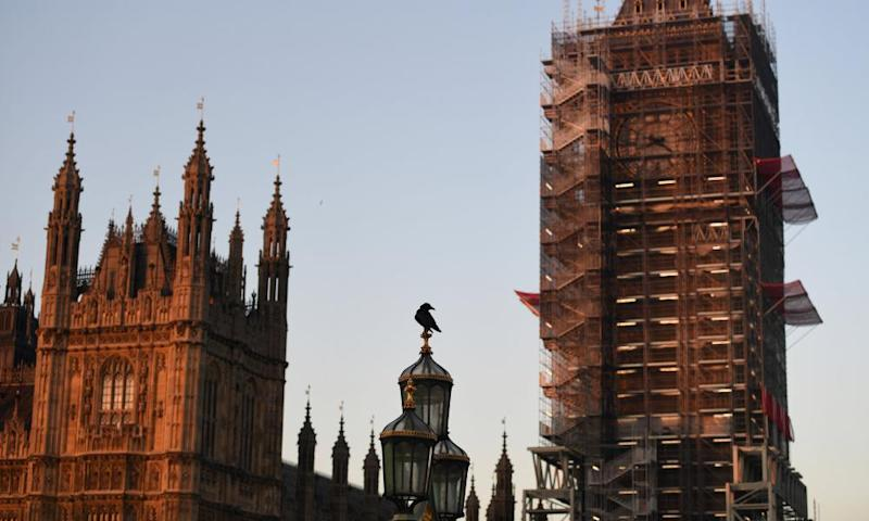 A crow perches on a street lamp on Westminster Bridge.