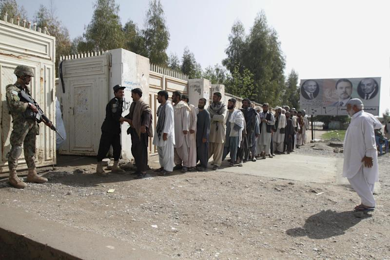 Afghan men line up for registration process before casting their votes at a polling station in Kandahar, Afghanistan, Saturday, April 5, 2014. Afghan voters lined up for blocks at polling stations nationwide on Saturday, defying a threat of violence by the Taliban to cast ballots in what promises to be the nation's first democratic transfer of power. (AP Photo/Allauddin Khan)
