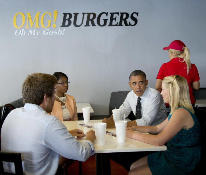President Barack Obama visits Emily Young, right, Maximo Soler, left, and Leslie Redmond, second from left, at OMG! Burgers, Thursday, Sept. 20, 2012, in Miami, Fla. (AP Photo/Carolyn Kaster)