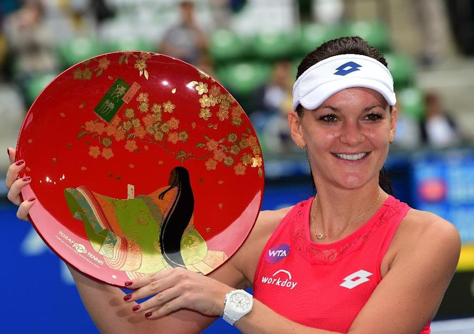Agnieszka Radwanska of Poland holds the championship trophy after beating Belinda Bencic of Switzerland in the women's singles final of the Pan Pacific Open, in Tokyo, on September 27, 2015 (AFP Photo/Yoshikazu Tsuno)