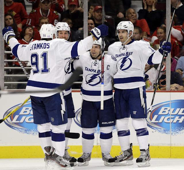 Tampa Bay Lightning's Teddy Purcell, right, celebrates with Steven Stamkos (91), Ryan Malone (12) and Martin St. Louis (26) after scoring during the third period of an NHL hockey game against the Chicago Blackhawks in Chicago, Saturday, Oct. 5, 2013. The Lightning won 3-2. (AP Photo/Nam Y. Huh)
