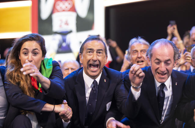 Mayor of Milan Giuseppe Sala, center, and members of Milan-Cortina delegation celebrate after winning the bid to host the 2026 Winter Olympic Games, during the first day of the 134th Session of the International Olympic Committee (IOC), at the SwissTech Convention Centre, in Lausanne, Switzerland, Monday, June 24, 2019. Italy will host the 2026 Olympics in Milan and Cortina d'Ampezzo, taking the Winter Games to the Alpine country for the second time in 20 years. (Xu Jinquan/Pool via AP)