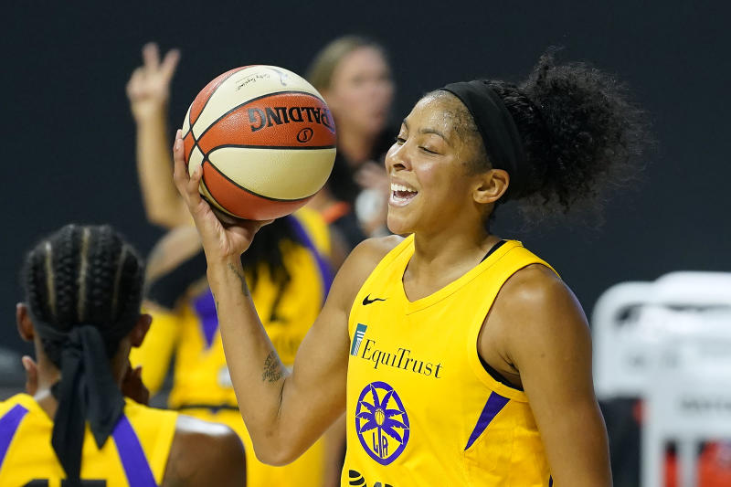 Candace Parker in a yellow Sparks jersey holds the basketball up.