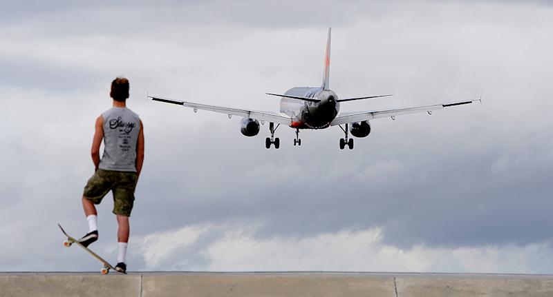 A Jetstar flight takes off as a young boy on a skateboard watches.