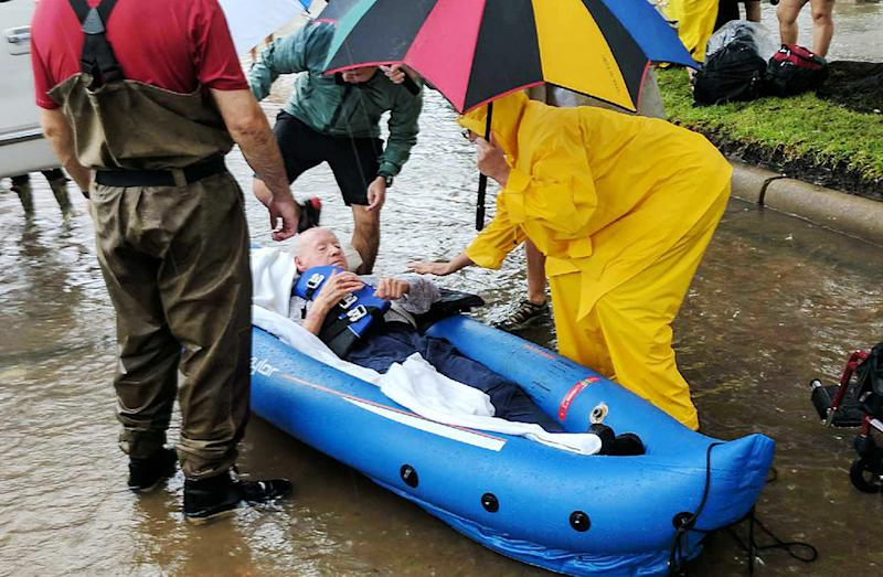 A person is rescued in a Houston neighborhood after water was released to ease overflowing on nearby reservoirs. (Roque Planas/HuffPost)