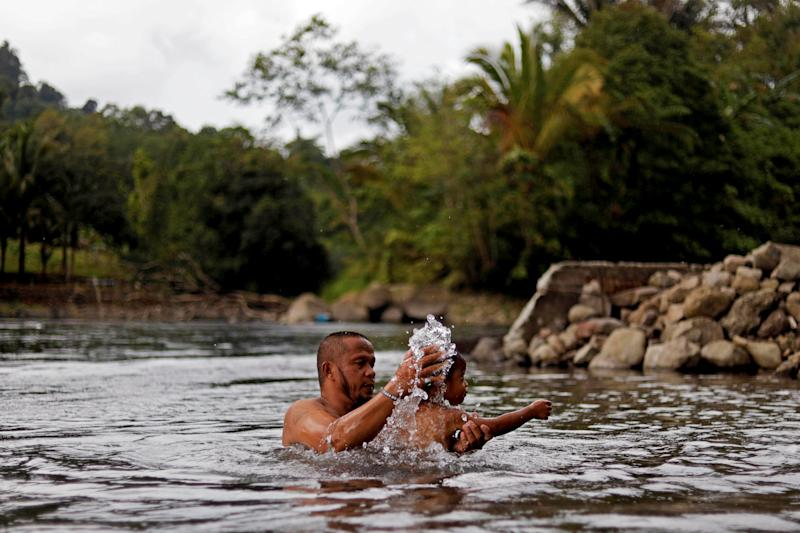 Mohammad Ali Acampong, 42, bathes his son in Rurug Agus, Marawi City, Lanao del Sur province, Philippines. (Photo: Eloisa Lopez/Reuters)
