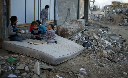 Palestinian children play on a mattress near ruins of houses which witnesses said were destroyed by Israeli shelling during most recent conflict in Gaza City