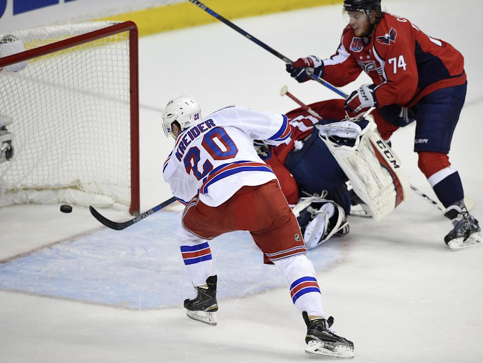 New York Rangers left wing Chris Kreider (20) scores his second goal of the period during the first period past Washington Capitals goalie Braden Holtby (70), center, and John Carlson (74) in Game 6 in the second round of the NHL Stanley Cup hockey playoffs, Sunday, May 10, 2015, in Washington. (AP Photo/Nick Wass)