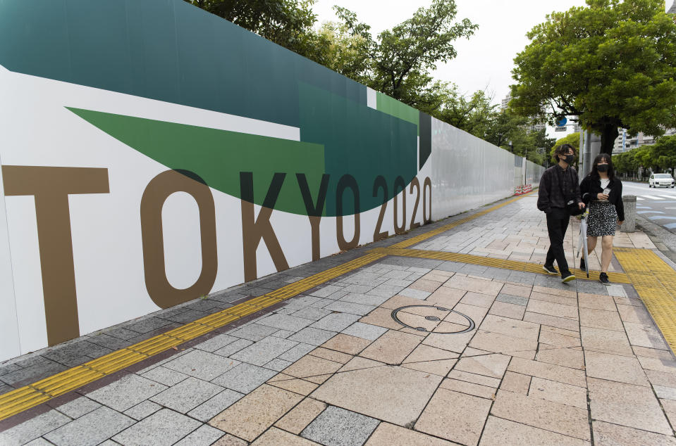 A man and a woman wearing face masks walk along the wall installed to close off a park being prepared for the Olympics and Paralympics Games in Tokyo on Thursday, July 1, 2021. They came to the park only to find out it was shut off. (AP Photo/Hiro Komae)