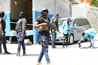 Members of the Haitian police and forensics look for evidence outside of the presidential residence on July 7, 2021 in Port-au-Prince, Haiti
