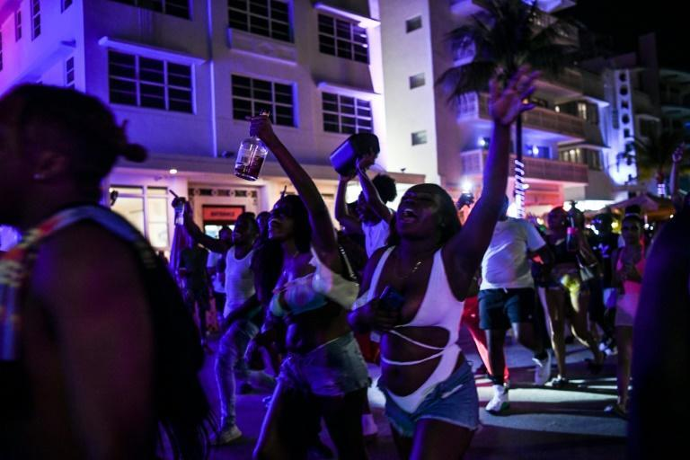 Revelers dancing in Miami Beach, Florida on March 17, 2021 -- a few days before a nightime curfew went into effect