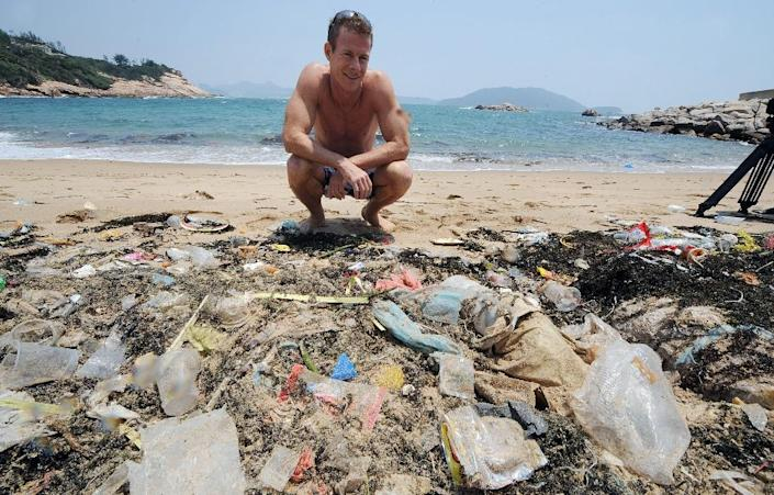 A conservationist looks at rubbish washed up on a beach on the south side of Hong Kong (AFP Photo/Mike Clarke)