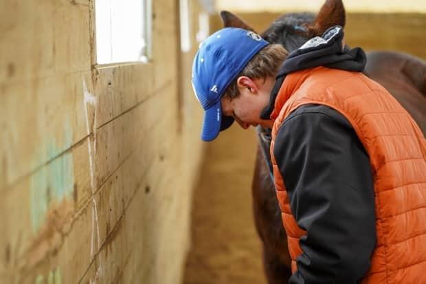 Alex, 15, enjoys a quiet moment with Nan, at Kindred Rescue Farm in North Gower, Ont.