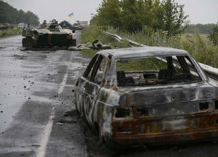 Destroyed vehicles are seen on a road near the Ukrainian army checkpoint just outside the eastern Ukrainian town of Slaviansk