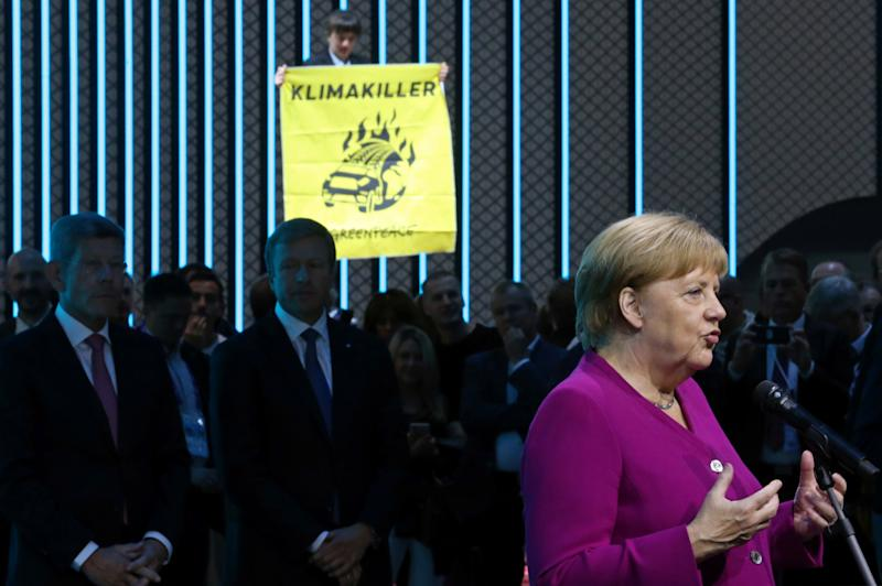 German Chancellor Angela Merkel speaks as a Greenpeace activist standing ontop of a displayed car protests against the global warming at the international Frankfurt Motor Show (IAA) in Frankfurt, Germany, September 12, 2019. REUTERS/Ralph Orlowski