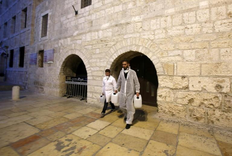 Employees from a private company emerge from the Church of the Nativity in Bethlehem after spraying disinfectant inside the holy site