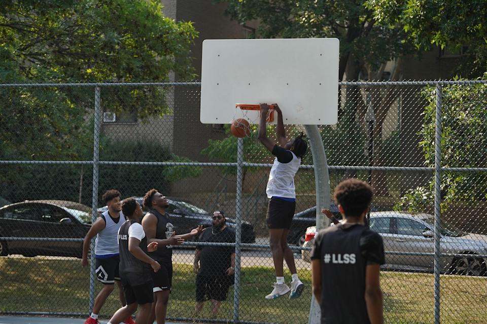 A player hanging off the basketball hoop