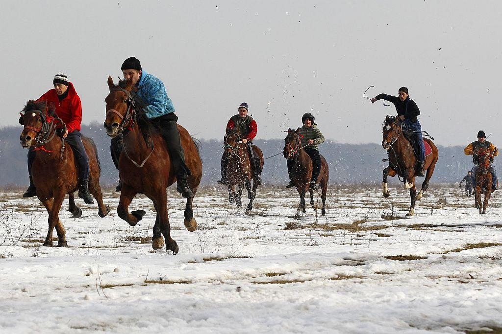 ROMANIA: Men ride their horses during the annual race organized by Orthodox believers on Epiphany Day in the Romanian village of Pietrosani, 45 km (28 miles) north of Bucharest, January 6, 2013. Epiphany Day falls on January 6 every year and it celebrates the end of Christmas festivities in Romania.