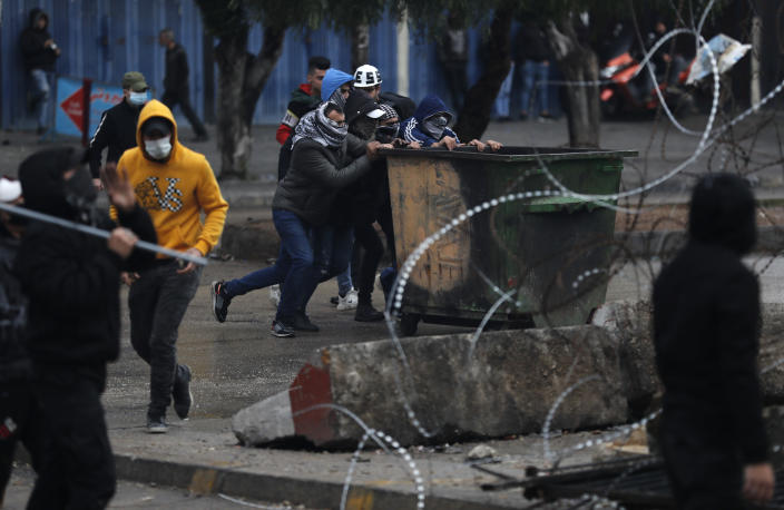 Protesters move a garbage container in an attempt to break the main door of an official government office during a protest against deteriorating living conditions and strict coronavirus lockdown measures, in Tripoli, north Lebanon, Thursday, Jan. 28, 2021. Violent confrontations between protesters and security forces over the last three days in northern Lebanon left a 30-year-old man dead and more than 220 people injured, the state news agency said Thursday. (AP Photo/Hussein Malla)