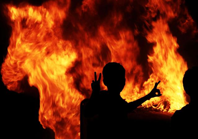 A Bahraini anti-government protester gestures next to burning garbage and old water storage tanks, after a march in Malkiya village, Bahrain, Tuesday, Dec. 4, 2012. (AP Photo/Hasan Jamali)