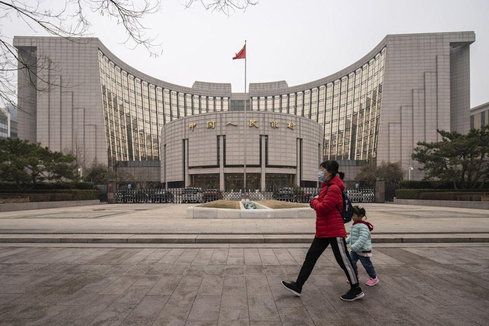 A woman and a child walk past the People's Bank of China (PBOC) building in Beijing on March 4. The bank is increasingly involved in overseeing Big Tech financial services while it also works on building out its own fintech infrastructure. Photo: Bloomberg
