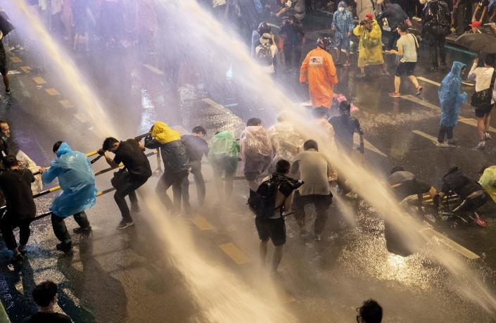 Pro democracy demonstrators face water canons as police try to disperse them from their protest venue in Bangkok, Thailand, Friday, Oct. 16, 2020. Thailand prime minister has rejected calls for his resignation as his government steps up efforts to stop student-led protesters from rallying in the capital for a second day in defiance of a strict state of emergency. (AP Photo/Gemunu Amarasinghe)
