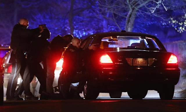 WATERTOWN, MA - APRIL 19: Police with guns drawn search for a suspect on April 19, 2013 in Watertown, Massachusetts. Earlier, a Massachusetts Institute of Technology campus police officer was shot and killed late Thursday night at the school's campus in Cambridge. A short time later, police reported exchanging gunfire with alleged carjackers in Watertown, a city near Cambridge. It's not clear whether the shootings are related or whether either are related to the Boston Marathon bombing. (Photo by Mario Tama/Getty Images)