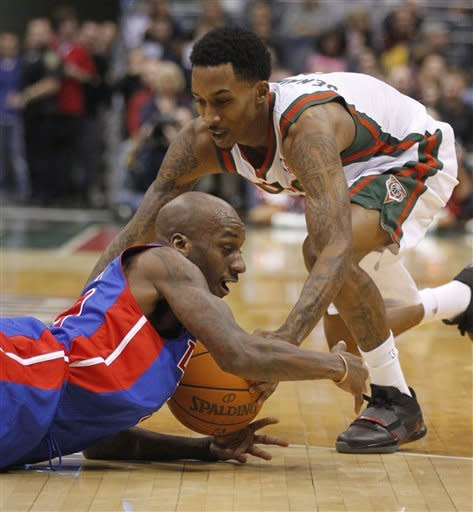 Milwaukee Bucks' Brandon Jennings, right, reaches for a loose ball with Detroit Pistons' Walker Russell, left during the second half of an NBA basketball game Monday, Jan. 30, 2012, in Milwaukee. (AP Photo/Jeffrey Phelps)