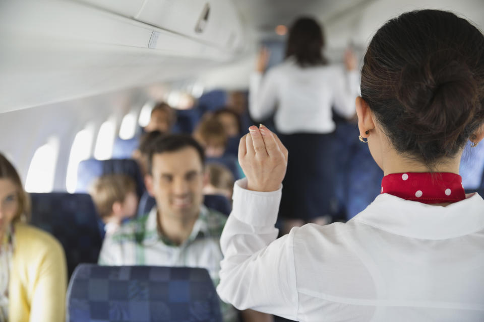 Rear view of flight attendant indicating exits to passengers in airplane