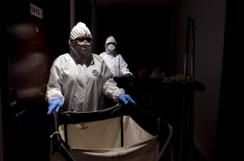 Employees of Vivenzo Hotel wearing protective suits, are seen while cleaning the hotel, amid the coronavirus disease (COVID-19) outbreak, in Belo Horizonte, Brazil, April 7, 2020. REUTERS/Washington Alves