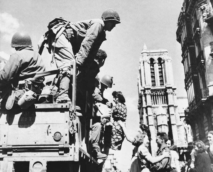 FILE - In this Aug. 28, 1944 file photo, French girls rush to greet American soldiers upon their arrival in Paris. The fighting for the liberation of Paris took place from August 19 to August 25, 1944. The French Resistance staged an uprising against the Nazis, leading attacks against German soldiers and vehicles and building barricades in the streets of the French capital. Towers of Notre Dame are in background at right. (AP Photo, File)