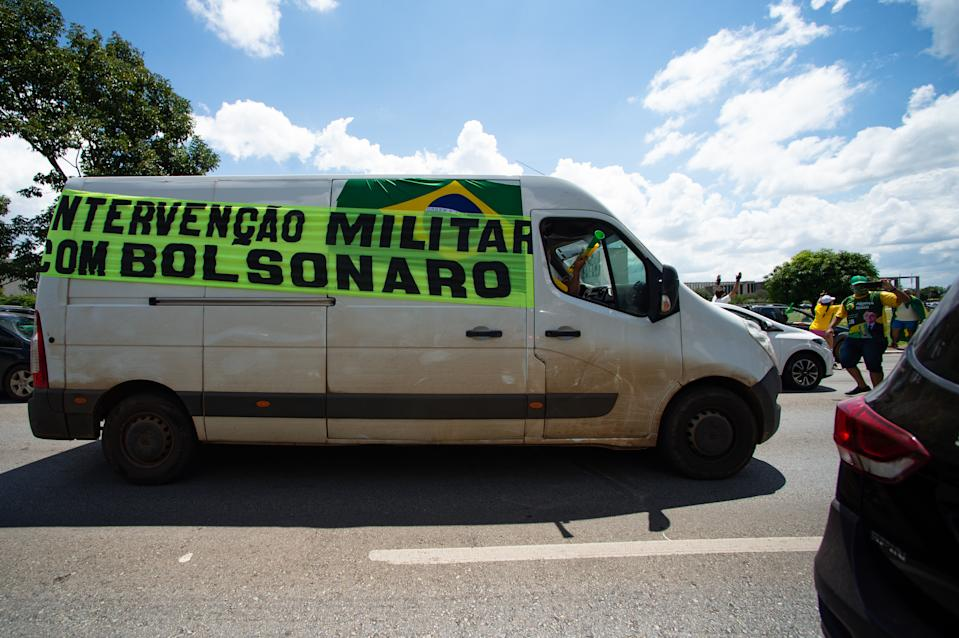 BRASILIA, BRAZIL - MARCH 14: Supporter of Brazilian President Jair Bolsonaro protest with written banner asking for military intervention during a motorcade and  demonstration in favor of the government amidst the coronavirus (COVID-19)pandemic in Esplanada dos Ministérios on  March 14, 2021 in Brasilia, Brazil. Brazil has over 11.439,000 confirmed positive cases of Coronavirus and has over 277,102 deaths. (Photo by Andressa Anholete/Getty Images)
