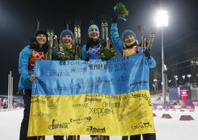 Ukraine's relay team Vita Semerenko, Juliya Dzhyma, Olena Pidhrushna and Valj Semerenko, from left, celebrate with a Ukrainian flag with writings on it after winning the gold during the women's biathlon 4x6k relay, at the 2014 Winter Olympics, Friday, Feb. 21, 2014, in Krasnaya Polyana, Russia. (AP Photo/Dmitry Lovetsky)