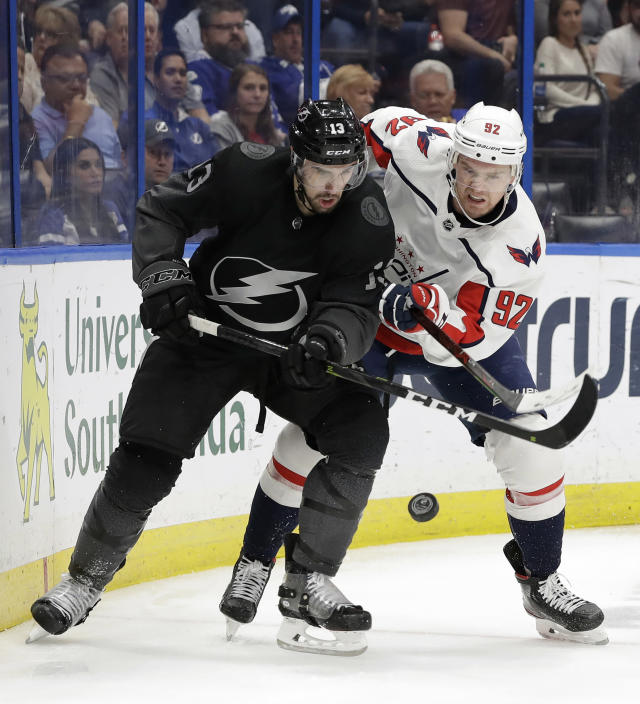 Tampa Bay Lightning center Cedric Paquette (13) and Washington Capitals center Evgeny Kuznetsov (92) battle for a loose puck during the second period of an NHL hockey game Saturday, March 30, 2019, in Tampa, Fla. (AP Photo/Chris O'Meara)