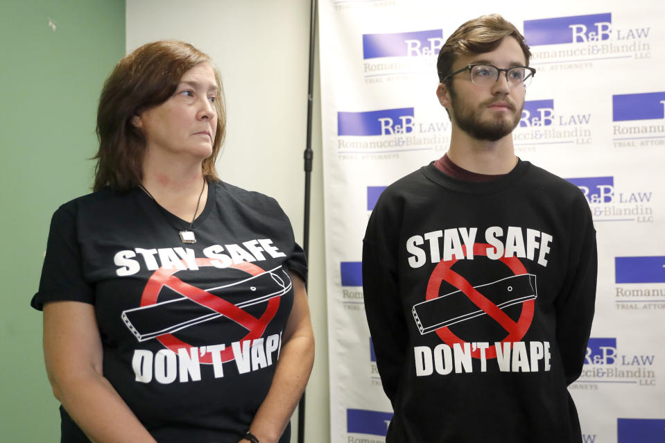Adam Hergenreder, right, and his mother Polly, attend a news conference where their attorney announced the filing of a civil lawsuit against e-cigarette maker Juul on Hergenreder's behalf Friday, Sept. 13, 2019, in Chicago. The lawsuit filed Friday in Lake County, Illinois, Circuit Court alleges Juul Labs, Inc., deliberately targeted young people through Instagram and other sites to suggest vaping can boost their social status. It also says Juul doesn't fully disclose their products contain dangerous chemicals. (AP Photo/Charles Rex Arbogast)