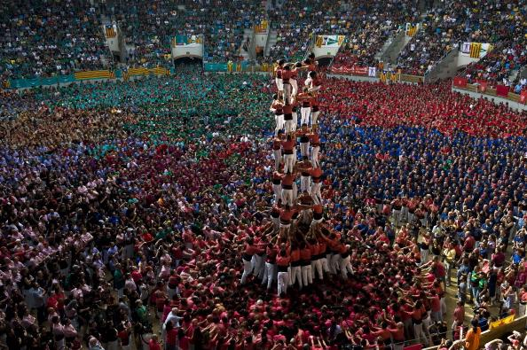 TARRAGONA, SPAIN - OCTOBER 07:  Members of the Colla 'Vella de Valls' climb up as they construct a human tower during the 24th Tarragona Castells Comptetion on October 7, 2012 in Tarragona, Spain. The 'Castellers' who build the human towers with precise techniques compete in groups, known as 'colles', at local festivals with aim to build the highest and most complex human tower. The Catalan tradition is believed to have originated from human towers built at the end of the 18th century by dance groups and is part of the Catalan culture.  (Photo by David Ramos/Getty Images)