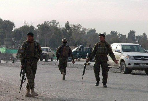 Afghan National Army (ANA) soldiers block a road at the site of a suicide attack in the city of Jalalabad in Nangarhar province. A Taliban suicide car bomber targeting NATO troops at an airport in eastern Afghanistan killed nine people Monday, the seventh day of violence over the burning of the Koran at a US airbase