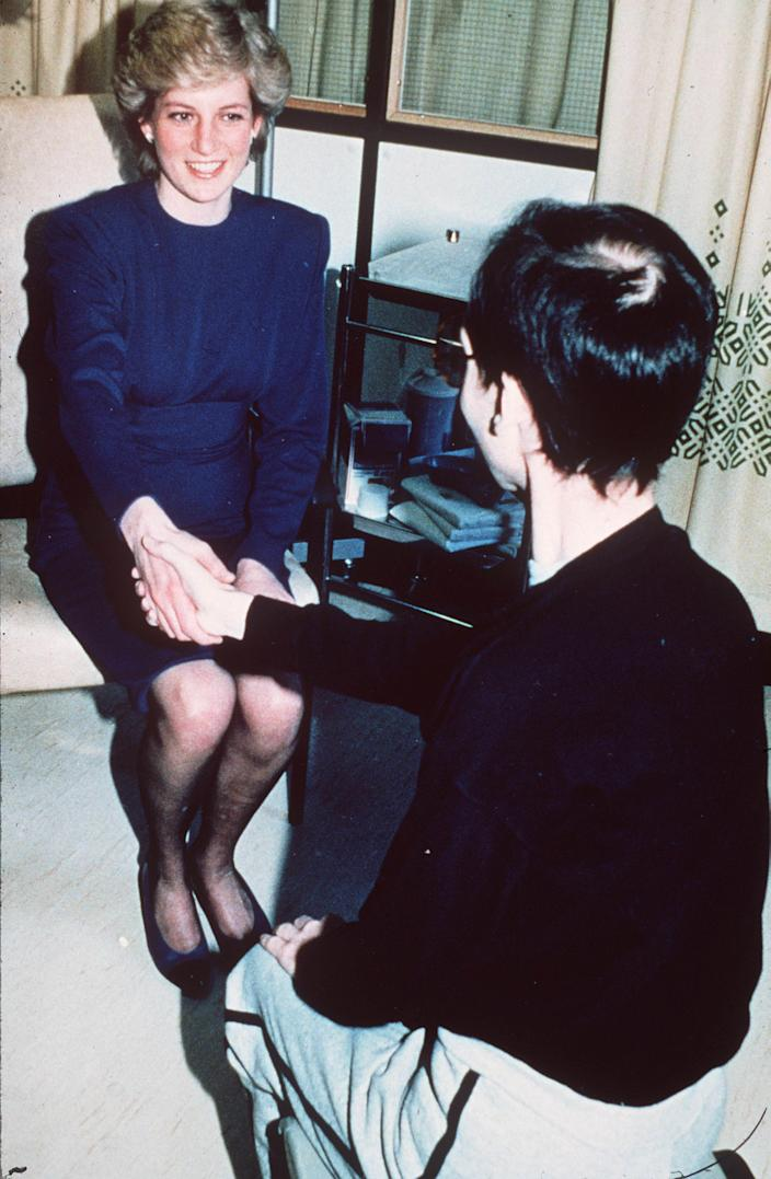 Diana, Princess of Wales, shakes hands with an AIDS victim as she opens a new ward for AIDS patients at the Middlesex Hospital on April 9, 1987, in London.