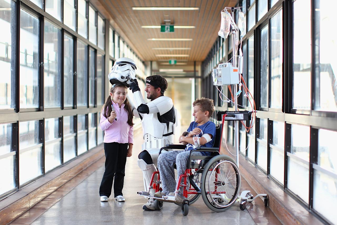Jacob French meets with patients Helena Kantarelis and Zak Brankstone at the Sydney Children's Hostpital on April 4, 2012 in Sydney, Australia. French today completed the over 5,000 km trek from Perth to Sydney on foot, donning a full body stormtrooper costume he successfully raised over $100,000 for the Starlight Children's Foundation. Since July 2011, Jacob has walked 10 hours a day, Monday to Friday, lost over 12kg in weight, and gone through seven pairs of shoes. The Starlight Children's Foundation provides programs to help lift the spirits of sick children in hospitals accross Australia.  (Photo by Cameron Spencer/Getty Images)