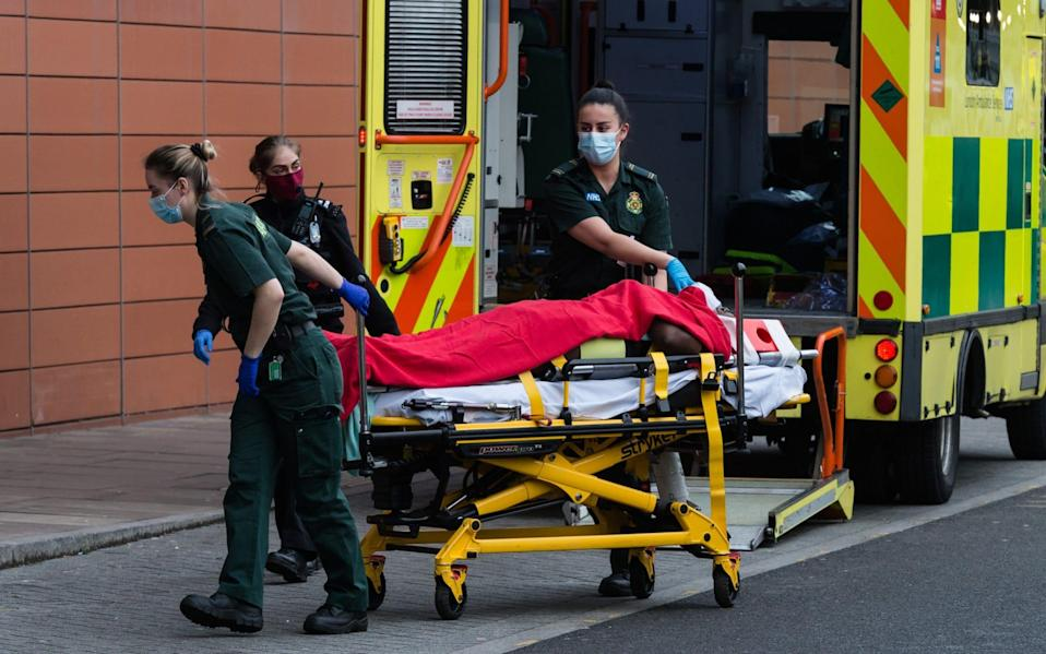 Paramedics transport a patient from the ambulance to the emergency department at the the Royal London Hospital - Barcroft Media