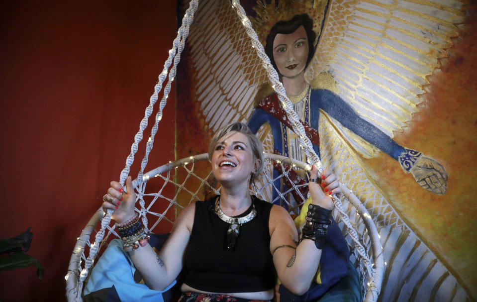 Rachel Berry sits in her self-decorated hammock swing next to her painting of her grandmother as an angel, Monday, July 6, 2020, in New York. Before the coronavirus pandemic, Berry worked as a bartender and waited tables, jobs that gave her enough time to work on her creative pursuits. But as New York City tries to reopen, there's concern that jobs for the city's creative class are no longer readily available. (AP Photo/Bebeto Matthews)