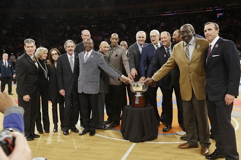 Phil Jackson, center, Jerry Luckas, center, left, and Bill Bradley, center right, and Earl Monroe, second from right, join other members of the 1972-73 World Champion New York Knicks team as they pose with the Walter Brown Championship trophy during halftime during of an NBA basketball game between the Knicks and the Milwaukee Bucks, Friday, April 5, 2013, in New York. (AP Photo/Frank Franklin II)