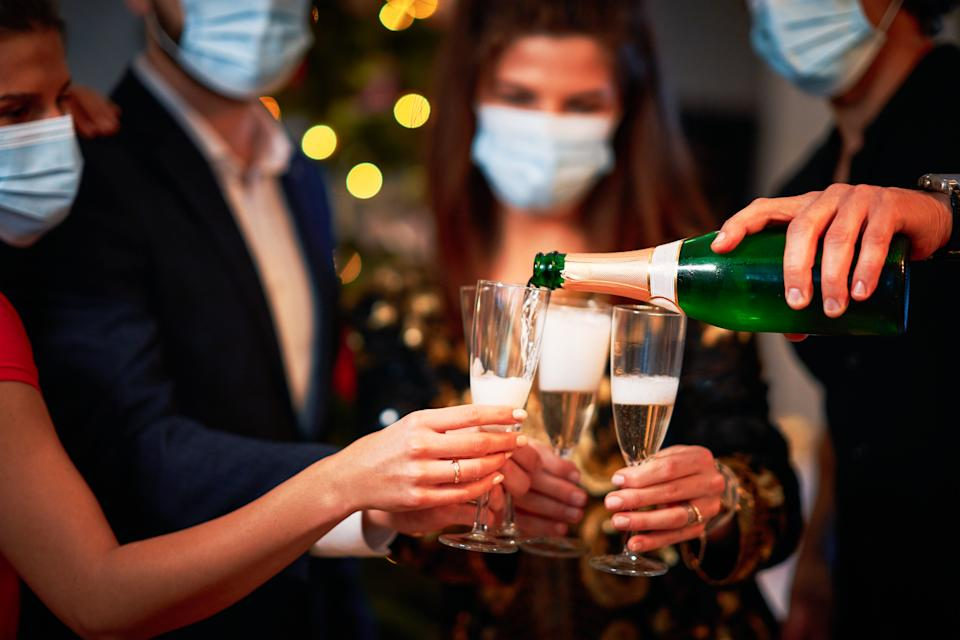 The CDC has issued new guidance for how to celebrate New Year's Eve, suggesting that those who want to gather indoors wear masks and stay six feet apart. (Photo: Getty Images)
