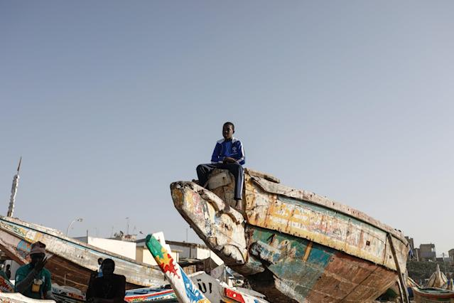 A boy sits on top of a fishermen pirogue in Yoff, commune of Dakar, Senegal March 14, 2018. Picture taken March 14, 2018. REUTERS/Zohra Bensemra