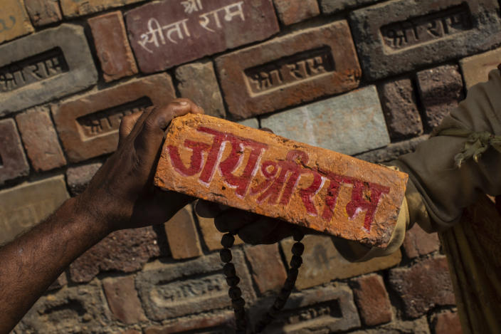 "FILE - In this Sunday, Nov. 25, 2018 photo, a man holds a brick reading ""Jai Shree Ram"" (Victory to Lord Ram) as bricks of the old Babri Mosque are piled up in Ayodhya, in the central Indian state of Uttar Pradesh. State-run broadcaster on Saturday, Nov. 9, 2019, said top court rules for disputed temple-mosque land for Hindus with alternate land to Muslims. Authorities increased security in Ayodhya, 550 kilometers (350 miles) east of New Delhi, and deployed more than 5,000 paramilitary forces to prevent any attacks by Hindu activists on Muslims, who comprise 6% of the town's more than 55,500 people. (AP Photo/Bernat Armangue, File)"