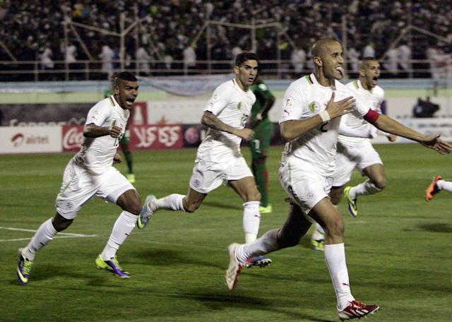 Algeria's Madjid Bougherra, right, reacts with his teammates after scoring a goal during their World Cup qualifying soccer match against Burkina Faso in Blida, nears Algiers, Tuesday, Nov. 19, 2013. Algeria won 1-0. ( (AP Photo/Anis Belghou)