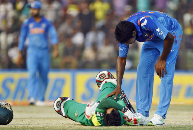 Bangladesh's Mushfiqur Rahim, on ground, reacts in pain after being hit by a ball as India's Varun Aaron tries to comfort him during the Asia Cup one-day international cricket tournament in Fatullah, near Dhaka, Bangladesh, Wednesday, Feb. 26, 2014. (AP Photo/A.M. Ahad)