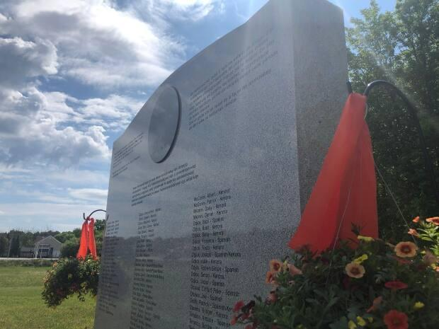 Orange ribbons flank a monument remembering the children from Kitigan Zibi who were forced to attend residential schools. The ribbons hang in remembrance of the 215 children whose remains were discovered in an unmarked burial site on the grounds of the former Kamloops Indian Residential School in B.C. (Christian Milette/Radio-Canada - image credit)